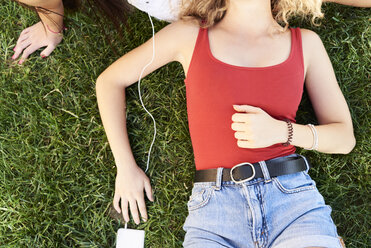 Young woman lying in grass with friend listening to music - IGGF00473