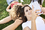 Young woman lying in grass with friends using cell phone - IGGF00476