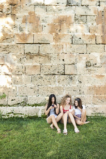 Three young women sitting at stone wall using cell phones listening to music - IGGF00479