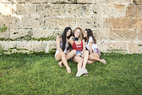 Three smiling young women sitting at stone wall taking a selfie - IGGF00482