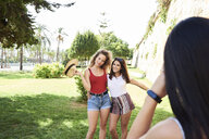 Spain, Mallorca, Palma, woman taking picture of best friends while having fun in a park in summer - IGGF00485