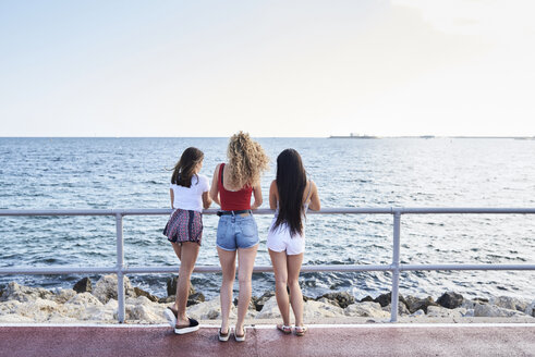 Spain, Mallorca, Palma, rear view of three young women standing at the sea - IGGF00488