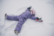 Young girl making snow angel in snow - ISF01392