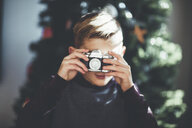 Boy taking photo, Christmas tree in background - ISF01395