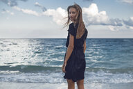 Portrait of young woman looking over her shoulder on beach, Odessa, Odessa Oblast, Ukraine - ISF01413