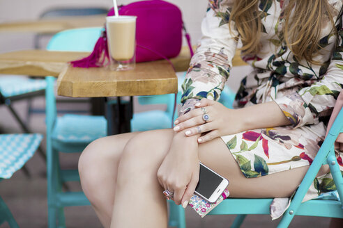 Stylish young woman at sidewalk cafe holding smartphone, cropped, Odessa, Ukraine - ISF01416