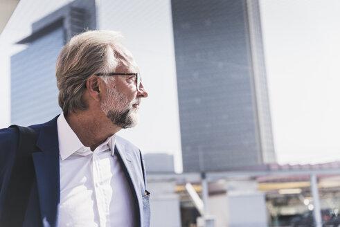 Confident mature businessman in the city looking around - UUF13647