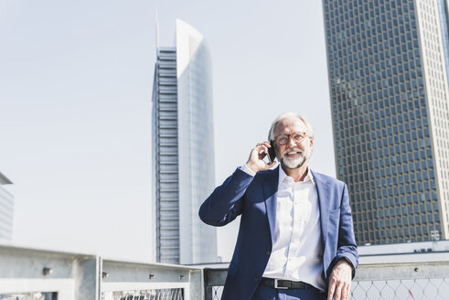 Smiling mature businessman in the city on cell phone - UUF13653