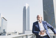 Mature businessman with cell phone in the city looking around - UUF13662