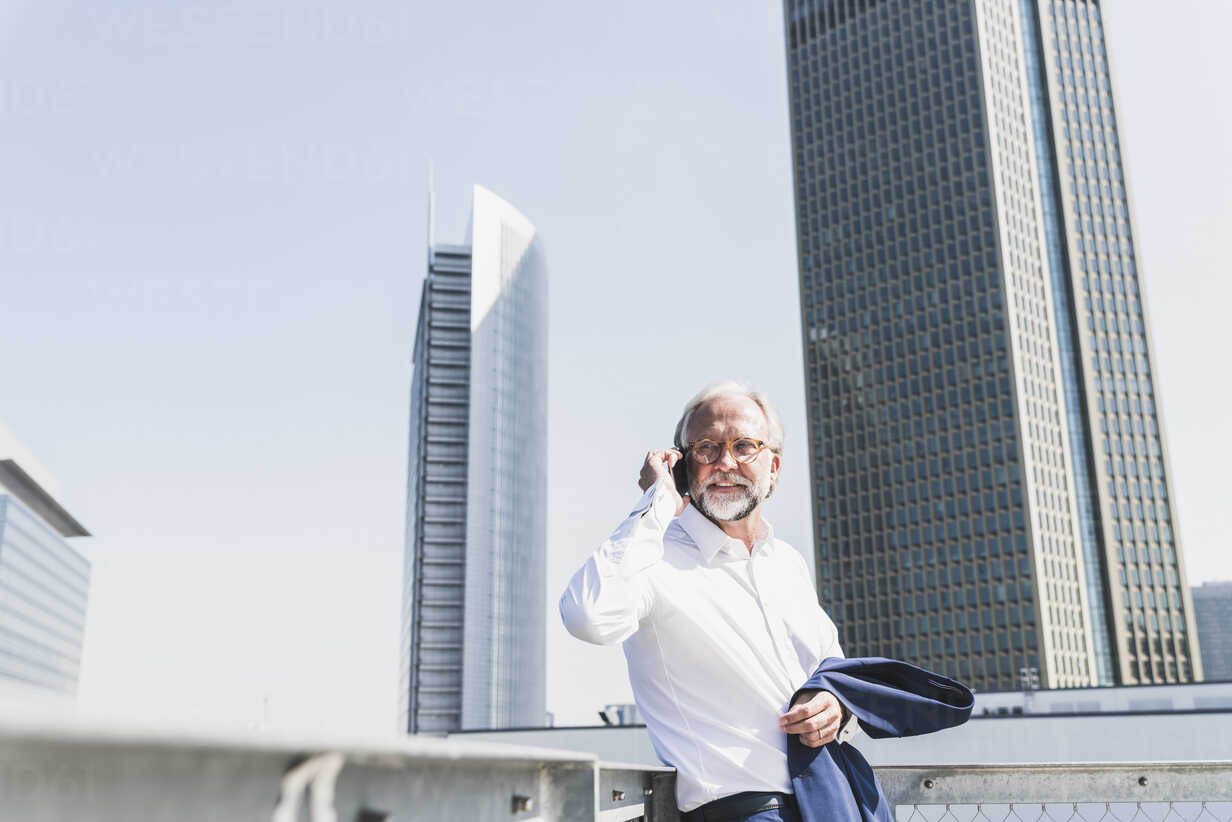 Confident mature businessman in the city on cell phone - UUF13665 - Uwe Umstätter/Westend61