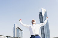 Happy mature businessman cheering in the city - UUF13668