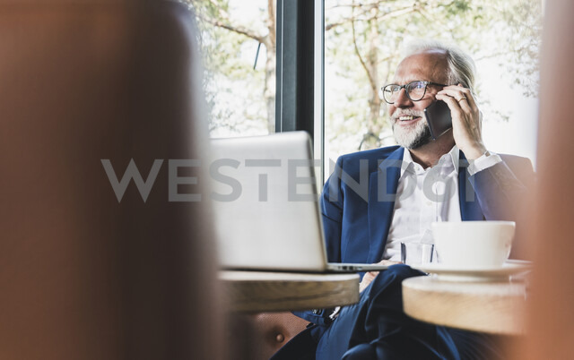 Mature businessman sitting at table in a cafe using cell phone and laptop - UUF13677