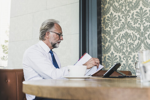 Mature businessman working at table in a cafe - UUF13683