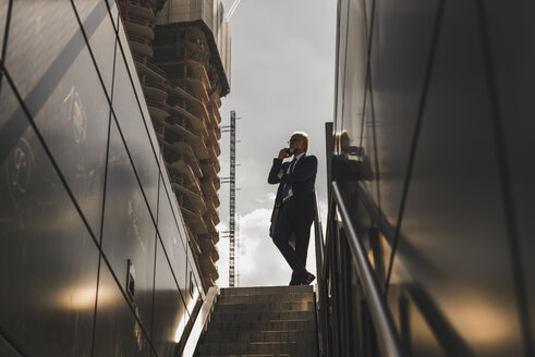 Mature businessman at staircase in the city on cell phone - UUF13686