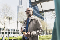 Mature businessman with snack and takeaway coffee in the city - UUF13695