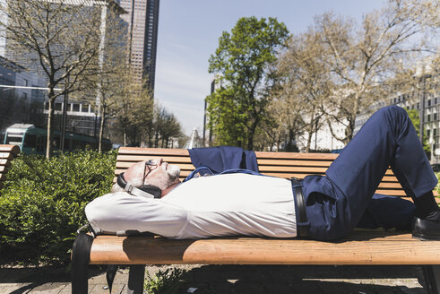 Mature businessman lying on a bench listening to music - UUF13698