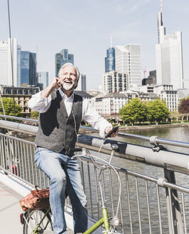 Happy mature man with earbuds, cell phone and bicycle on bridge in the city - UUF13704