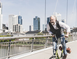 Happy mature man on bicycle crossing bridge in the city - UUF13707