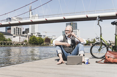 Mature man with laptop, earbuds and bicycle sitting at the riverside in the city - UUF13710