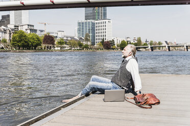 Mature man with laptop and earbuds sitting at the riverside in the city - UUF13713