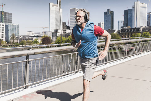 Mature man with headphones running on bridge in the city - UUF13719
