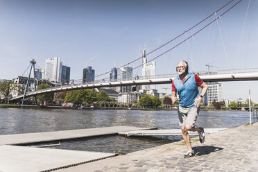 Mature man with headphones running at the riverside in the city - UUF13722