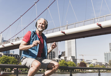 Happy athletic mature man with headphones sitting at the riverside in the city - UUF13725