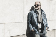 Portrait of fashionable mature man wearing sunglasses leaning against a wall - UUF13728