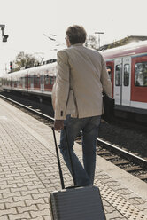 Rear view of mature businessman walking at train platform with suitcase - UUF13731