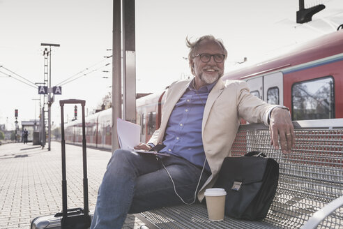 Smiling mature businessman sitting at train station with cell phone, earbuds and notebook - UUF13734
