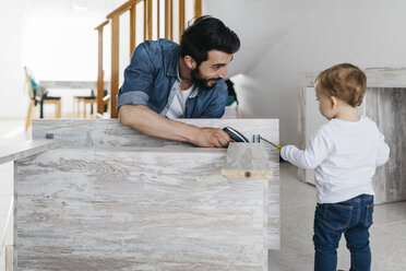 Father and daughter assembling a wooden table at home - JRFF01642