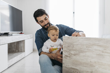 Father and daughter assembling a wooden table at home - JRFF01645