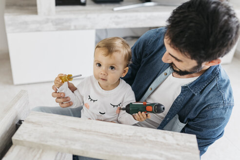 Father and daughter assembling a wooden table at home - JRFF01648