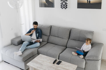 Father working in the living room while the daughter watching the tablet - JRFF01657