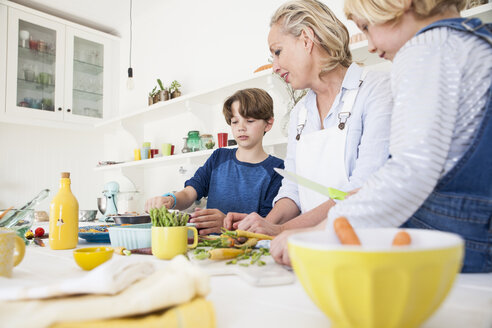 Mature woman preparing vegetables at kitchen table with son and daughter - CUF05730