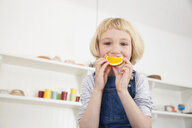 Portrait of cute girl in kitchen holding orange slice to her mouth - CUF05763