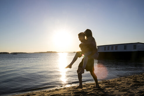 Backlit young man giving girlfriend piggyback on beach at sunset - CUF05886