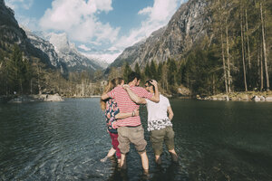 Rear view of three young adult friends ankle deep in mountain lake, Lombardy, Italy - CUF05898