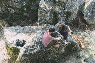 High angle view of two bouldering friends sitting on boulder, Lombardy, Italy - CUF05907