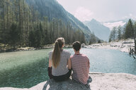 Rear view of young hiking couple looking out at mountain lake, Lombardy, Italy - CUF05910