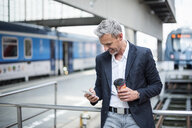 Mature businessman looking at smartphone on train station platform - CUF05937