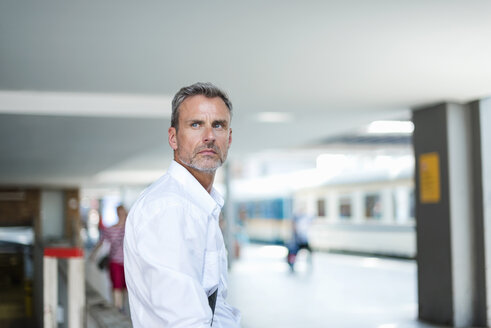 Mature businessman looking over his shoulder from train station platform - CUF05940
