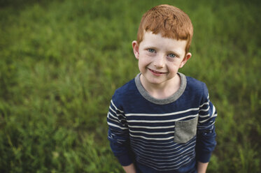 Portrait of red haired boy standing on grass - CUF05964