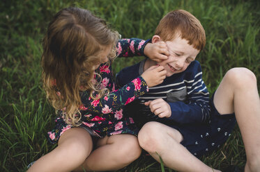 Boy and sister play fighting in field - CUF05970