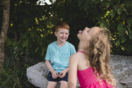 Girl sticking tongue out at brother sitting on rock - CUF05973