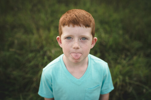 Portrait of red haired boy sticking out tongue - CUF05976