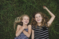 Overhead portrait of girl and her sister lying on grass - CUF05982