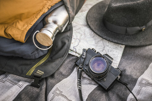 Still life of blanker, SLR camera, drinking flask and hat - CUF06267