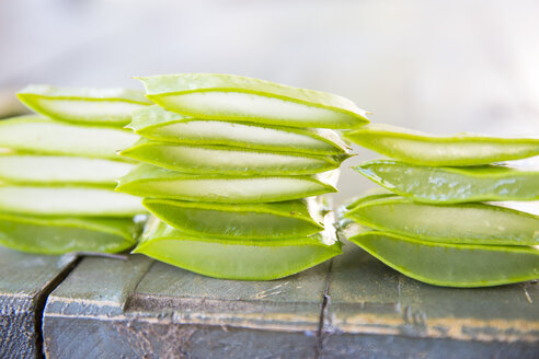 Stacked sliced aloe leaves on table in handmade soap workshop - CUF06291