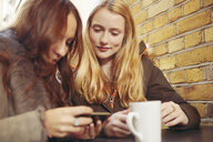 Two female friends, sitting outdoors, having coffee, looking at smartphone - CUF06363